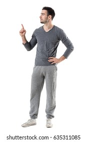 Fit sport man in sweat pants and gray shirt pointing finger up looking at copyspace. Full body length portrait isolated on white studio background.
