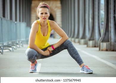 fit sports woman in fitness clothes on Pont de Bir-Hakeim bridge in Paris relaxing after workout.
