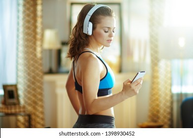 fit sports woman in headphones in sport clothes at modern home using online fitness training program in smartphone.