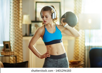 fit sports woman in headphones in sport clothes in the modern house doing functional training exercises.