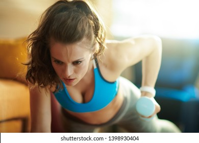 fit sports woman in sport clothes with blue dumbbell workout at modern home.