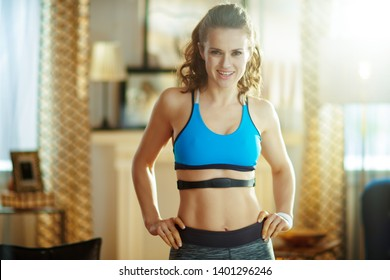 fit sports woman in sport clothes at modern home wearing heart rate monitor.