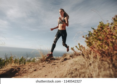 Fit sports woman sprinting over rocky trail on mountain. Woman running downhill on mountain path.