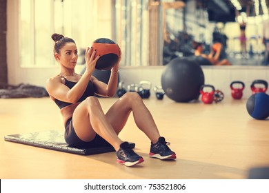 Fit sportswoman doing exercise with ball for six pack