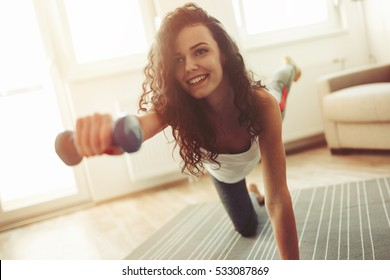 Fit sportswoman exercising and training at home
