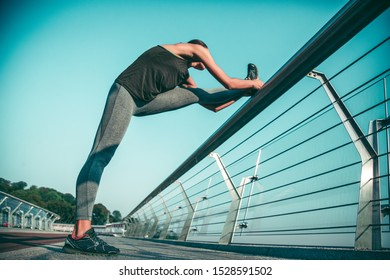 Fit sportswoman putting foot on the bridge banister and leaning towards it