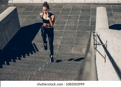 Fit sportswoman running up the steps. Female runner exercising on staircase outdoors.