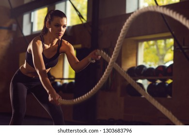 Fit, sporty and athletic sportswoman working in a gym. Woman training using battle ropes. Sports, athletics and fitness concept.