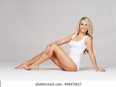 Fit and sporty beautiful woman with perfect shape. Girl in white underwear on the floor. Healthy lifestyle, sport, healthcare, nutrition and diet concept.
