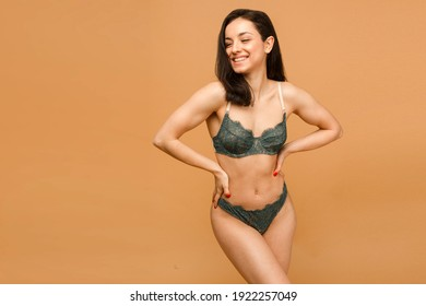Fit and sporty girl in underwear. Beautiful and healthy woman posing over beige background. Sport, fitness, diet, weight loss and healthcare concept