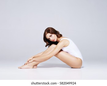 Fit and sporty girl in underwear. Beautiful and healthy woman posing over white background. Sport, fitness, diet, weight loss and healthcare concept.