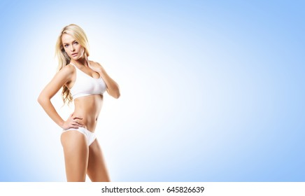 Fit and sporty girl in white underwear. Beautiful and healthy woman posing over blue background. Sport, fitness, diet, weight loss and healthcare concept.