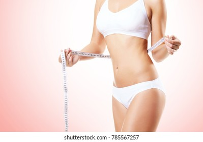 Fit and sporty girl in white underwear. Beautiful and healthy woman posing. Sport, fitness, diet, weight loss and healthcare concept.