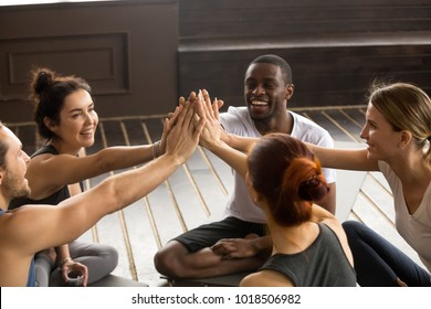 Fit sporty happy multicultural people giving high five at yoga training, motivated multiracial group unite joining hands together as concept of team support in fitness achievements and mindful life