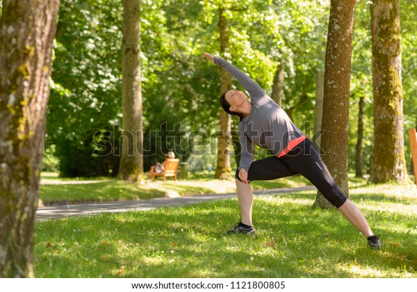 Fit sporty mature woman doing yoga exercises in a park one arm in a full stretch in a health and fitness concept