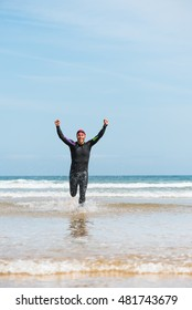 Fit sporty open water swimmer man running off shore on a beach rising arms up in victory sign after swimming triathlon competition exercise routine workout.
