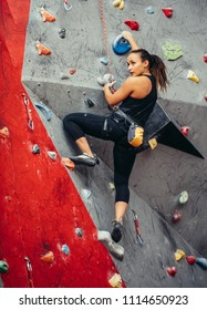 Fit sporty student girl equipped with safety rope and harness moving up at rock climbing wall at the gym. Red and grey colour background