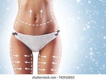 Fit and sporty woman with beautiful and slender body over seasonal Christmas background with winter snow. Health, diet and sport concept.