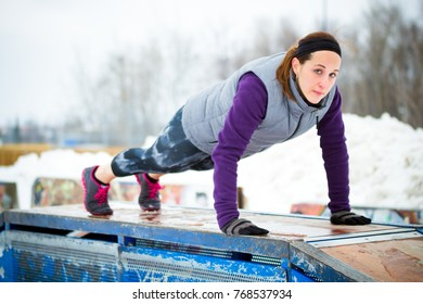 Fit sporty woman doing push-up strenght exercise at outdoor urban park in winter