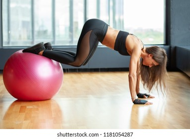 fit sporty woman in gym doing abs exrcise on fit ball
