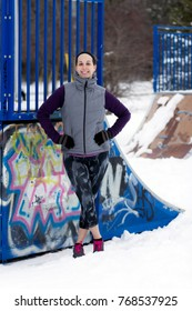 Fit sporty woman outdoors in winter running gear at urban park with graffiti. Fit healthy lifestyle concept.
