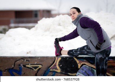Fit sporty woman outdoors in winter running gear at urban park with graffiti stretching. Fit healthy lifestyle concept.