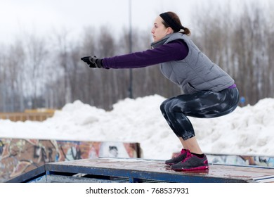 Fit sporty woman outdoors in winter running gear at urban park doing squat exercises. Fit healthy lifestyle concept.