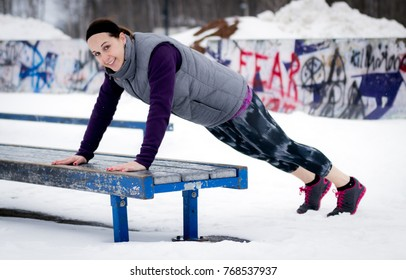 Fit sporty woman outdoors in winter running gear at urban park doing push-up exercises. Fit healthy lifestyle concept.