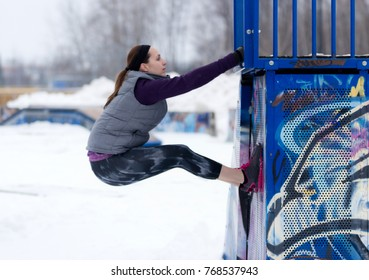 Fit sporty woman outdoors in winter running gear at urban park doing climbing exercises. Fit healthy lifestyle concept.