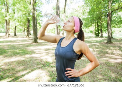 Fit sporty woman refreshing by bottle of water in nature healthy lifestyle.