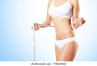 Fit and sporty woman in white underwear. Beautiful and healthy woman measuring her perfect body over cyan background. Sport, fitness, diet, weight loss and healthcare concept.