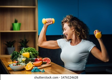 Fit and strong girl, model holding dumbbells, with fresh salade on table, healthy eat time.