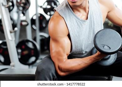 Fit starker Mann, der Biceps Curling im Fitnessraum macht