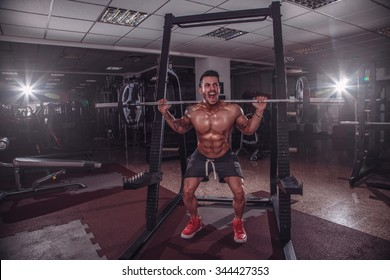 Fit and strong man doing squats in the gym.
