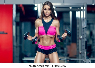 Fit strong muscular young woman lifting weights working out with dumbbells flexing her arms in modern gym