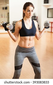 Fit and strong young woman with abs lifting a pair of dumbbells in a gym as part of her workout