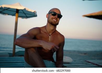 Fit Tanned Man Smiling at the beach. Holiday Concept.
