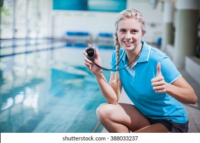 Fit trainer showing stopwatch with thumbs up at the pool