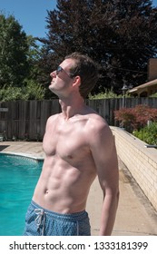 Fit white man with defined abs standing on deck of an outdoor swimming pool in blue swimming trunks and aviator sunglasses. Sexy man posing by the swimming pool looking up at the sun.
