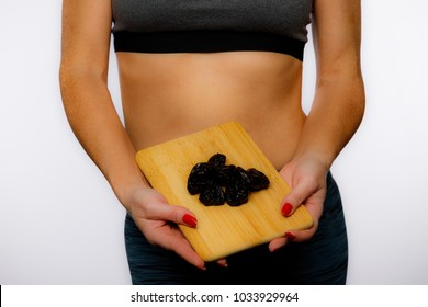 Fit Woman In Activewear Holding Prunes On A White Background