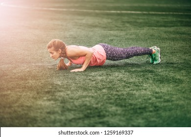 Fit woman in bright sports clothes to do burpees on the green grass