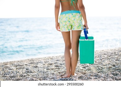 Fit woman carrying cooler box,portable fridge on the beach.Fit slim healthy woman in flower shorts for going to the beach with cooler with healthy food and drinks.Carrying food and drinks to the beach