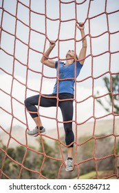 Fit woman climbing a net during obstacle course in boot camp