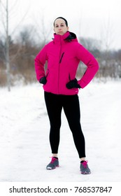 Fit woman with determined look in cold weather workout attire near forest during winter. Fitness and wellness lifestyle concept.
