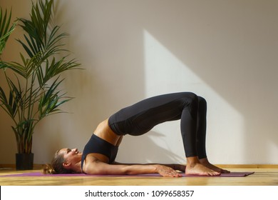 fit woman doing bridge exercise in stretching studio