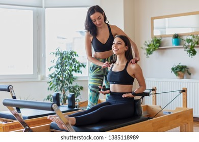 A Fit Woman Doing Complicated Exercises on Pilates Bed with Female  Instructor at  Gym