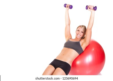 A fit woman doing a dumbbell routine on a red exercise ball