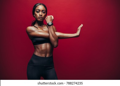 Fit woman doing exercise against red background. African female doing arm stretching exercise to keep a good flexibility of her biceps.
