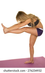 A fit woman doing a leg stretch, bending over.