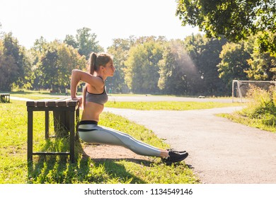 Fit woman doing push-ups at the park.